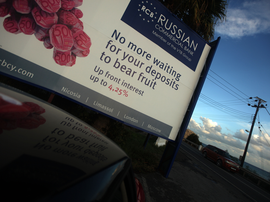 A car drives past a billboard promoting a Russian bank on a main road in the southern Cypriot port of Limassol earlier this month. Russian and Ukrainian investors have a major presence in Cyprus. (AFP/Getty Images)