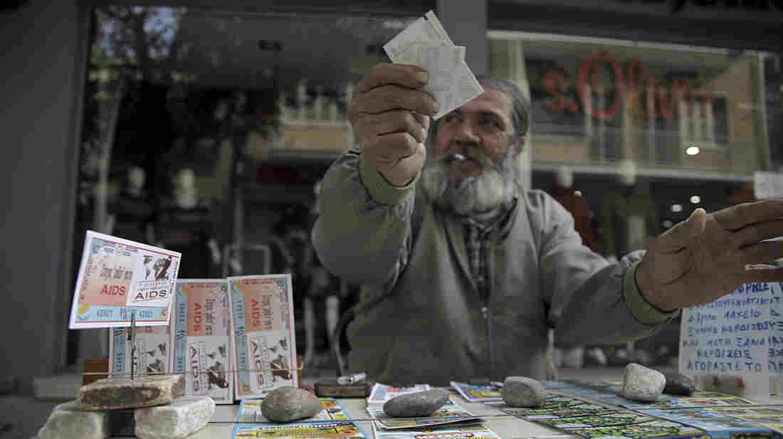 A man sells lottery tickets in Nicosia, the capital of Cyprus, last week. The island has been divided since 1974. Now, the once-poor north has strong economic growth while the once-wealthy south is set to become the fourth eurozone country receiving a bailout.