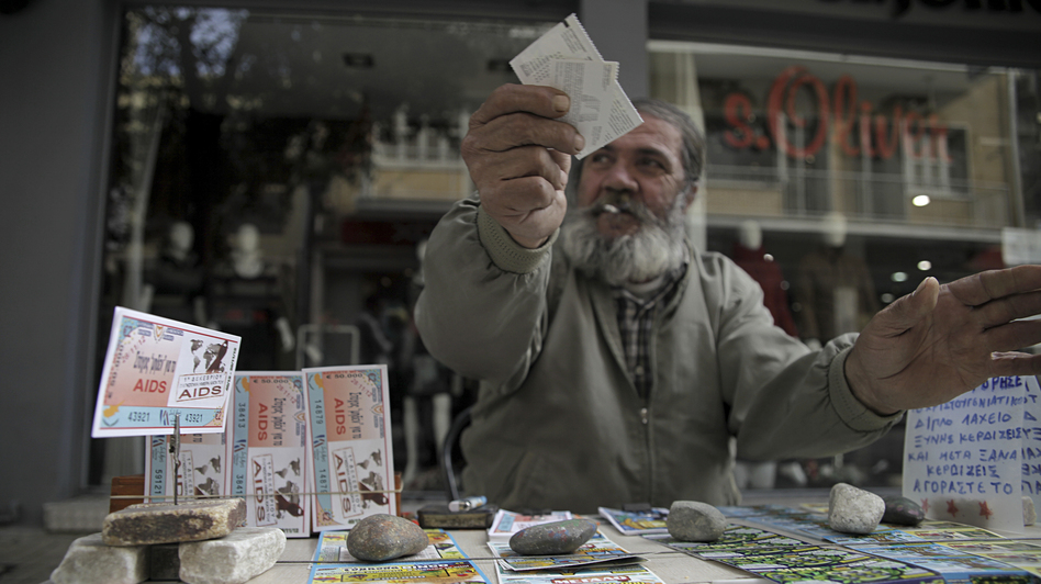 A man sells lottery tickets in Nicosia, the capital of Cyprus, last week. The island has been divided since 1974. Now, the once-poor north has strong economic growth while the once-wealthy south is set to become the fourth eurozone country receiving a bailout. (AFP/Getty Images)
