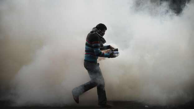 A cloud of tear gas surrounds a protester earlier today near Cairo's Tahrir Square. (AFP/Getty Images)
