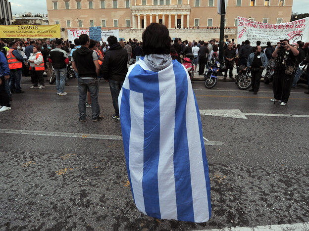Nov. 7: A protester wrapped in a Greek flag stands in front of the parliament in Athens. Today's agreement may not bring an end to anti-austerity protests in Greece.