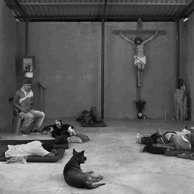 Weary migrants rest in the makeshift chapel of the Hermanos en El Camino migrant shelter in the small town of Ixtepec, in the Mexican state of Oaxaca. June 2009.