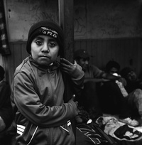 A 9-year-old Guatemalan boy traveling with his mother waits for a train with other migrants seeking shelter from the elements under the tin roof of a concession stand near the tracks in Orizaba. July 2010.