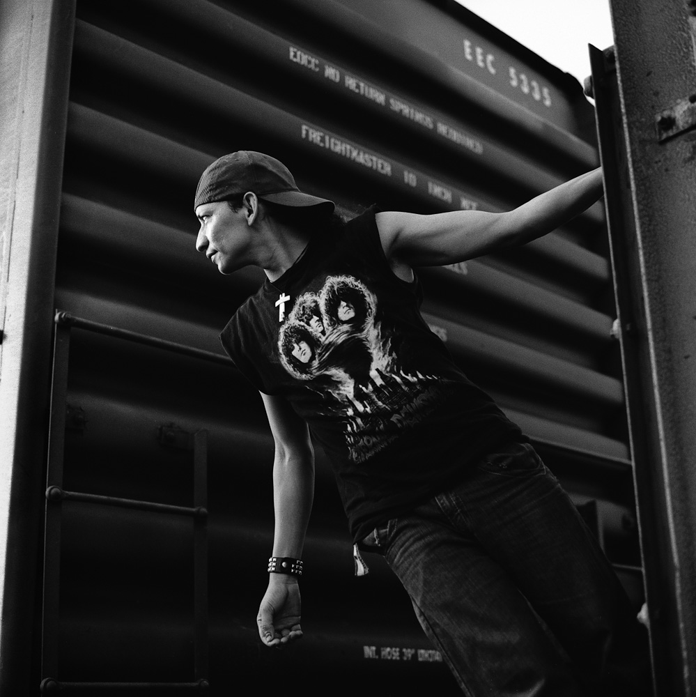 A Salvadoran migrant hangs onto a rail between two boxcars in a rail yard. Some travel approximately 150 miles by foot to Arriaga in Chiapas, Mexico, in order to avoid Mexican immigration checkpoints. July 2010.