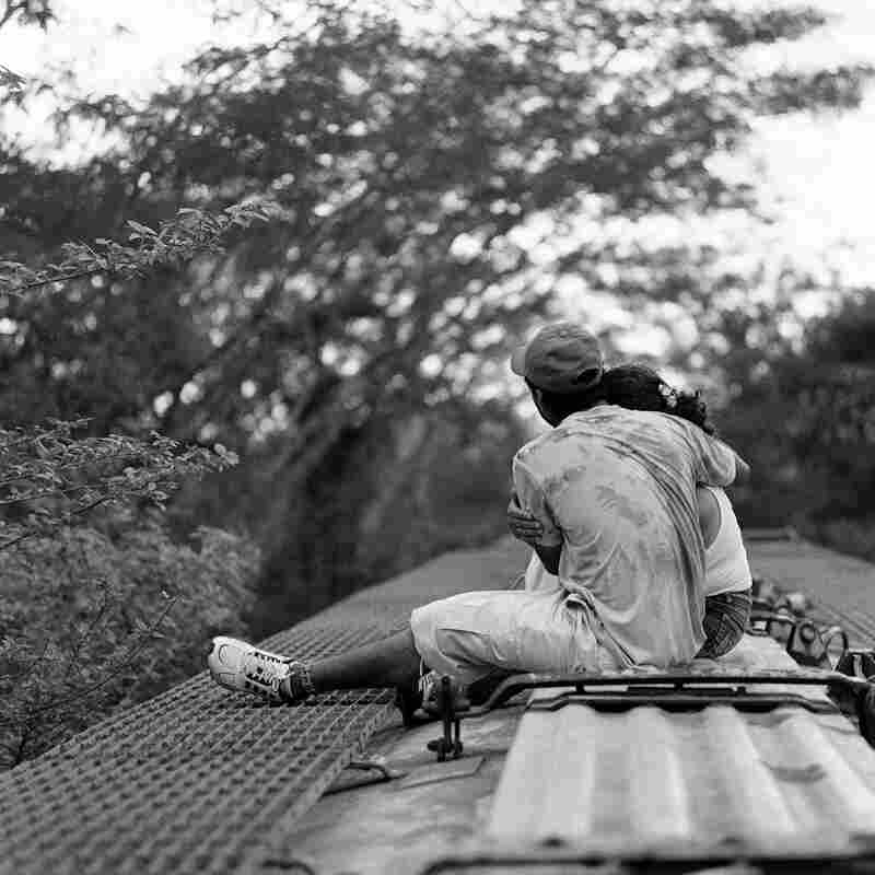 A Guatemalan migrant couple embraces on top of a northbound freight train while traveling through the Mexican state of Chiapas. June 2009.