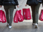 If they're confident, they will shop: Two women carry shopping bags down Manhattan's 34th St. last week.