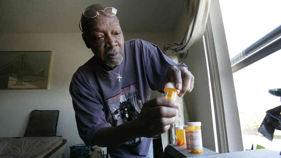 Keith Gresham, 65, lines up four medications he takes at his home in