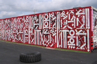 Los Angeles artist RETNA developed his own alphabet from gang writing and calligraphy. The top line on this RETNA mural reads