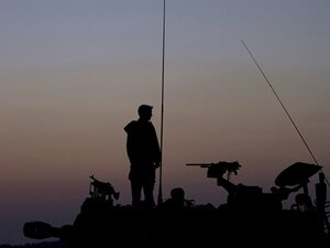After a week of recent fighting between Israel and Hamas, an Israeli soldier stands on top of a mobile