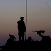 After a week of recent fighting between Israel and Hamas, an Israeli soldier stands on top of a mobile artillery unit in a position near the Israel Gaza border.