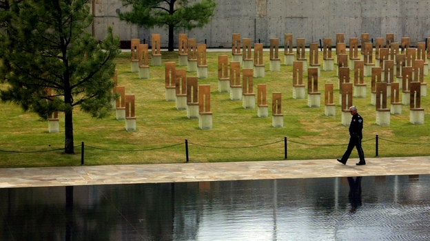 A security guard walks along the edge of the reflecting pool, past the field of 168 empty chairs, at the Oklahoma City National Memorial in Oklahoma City. (AP)