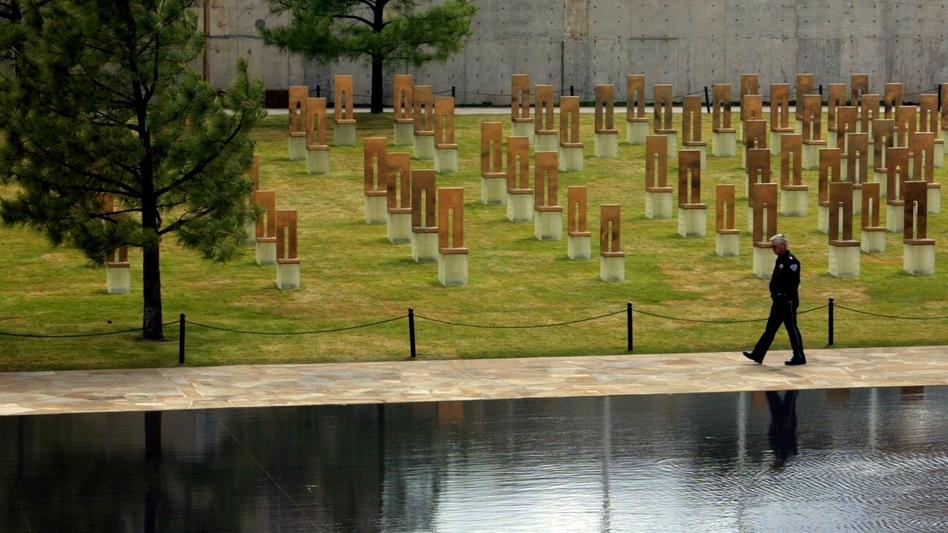 A security guard walks along the edge of the reflecting pool, past the field of 168 empty chairs, at the Oklahoma City National Memorial in Oklahoma City.