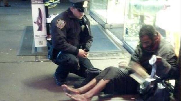 NYPD officer Lawrence DePrimo gives a pair of boots to a barefoot man in Manhattan. (NYPD via Facebook)