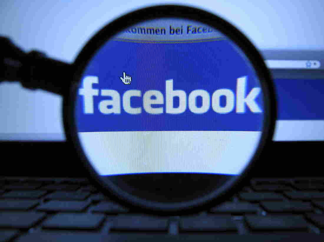 A magnifying glass is posed over a monitor displaying a Facebook page in Munich.