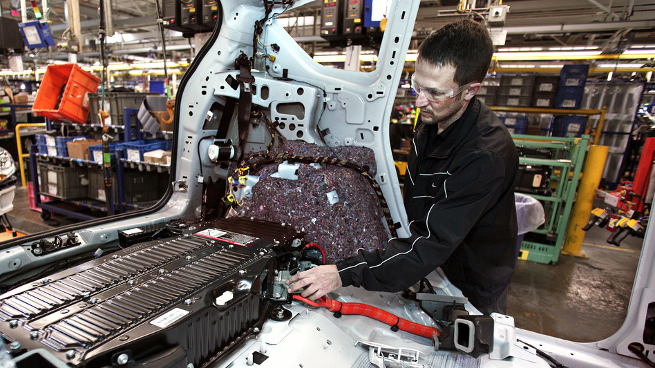 Better than expected: Economic growth was higher in the third quarter than first thought. Here, a worker at a Ford plant in Michigan plugs a batter into a Ford C-MAX plug-in hybrid vehicle. (Getty Images)