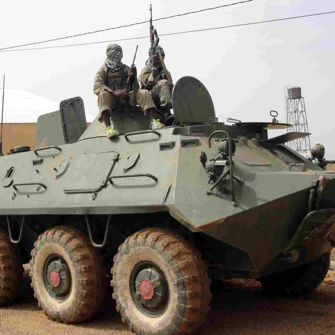 Fighters of the Islamist group, the Movement for Oneness and Jihad in West Africa guard a tank abandoned by the Malian army on Aug. 7.