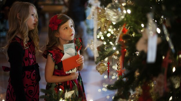 """Lauren Rae (left) and Olivia Marlow look at the ornaments in the Grand Foyer during the first viewing of the White House 2012 holiday decorations in Washington, D.C., on Wednesday. This year's theme is """"Joy to All."""" (AFP/Getty Images)"""