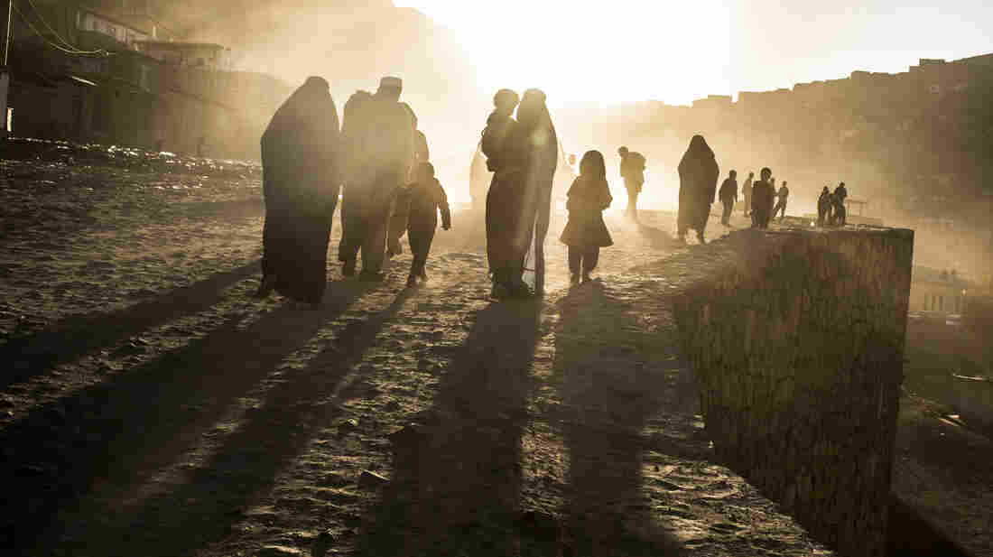 Afghan families walk along a dusty road in Kabul, the Afghan capital, last month. In the latest in a series of dramatic inflows and outflows, more Afghans are leaving the country than returning, fueled by unease about next year's withdrawal of NATO forces.