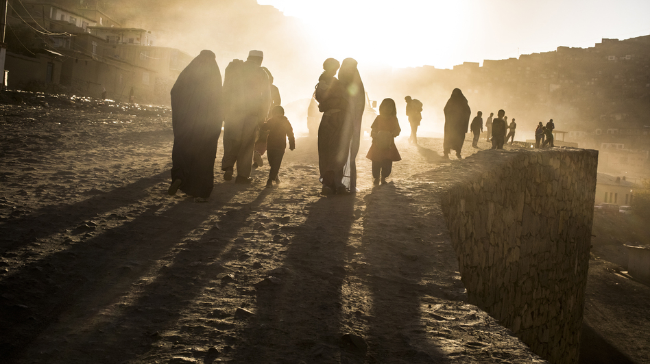 Afghan families walk along a dusty road in Kabul, the Afghan capital, last month. In the latest in a series of dramatic inflows and outflows, more Afghans are leaving the country than returning, fueled by unease about next year's withdrawal of NATO forces. (Getty Images)