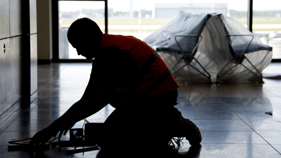 A carpenter works in the unfinished departure hall of the airport on Sept. 11. (AFP/Getty Images)