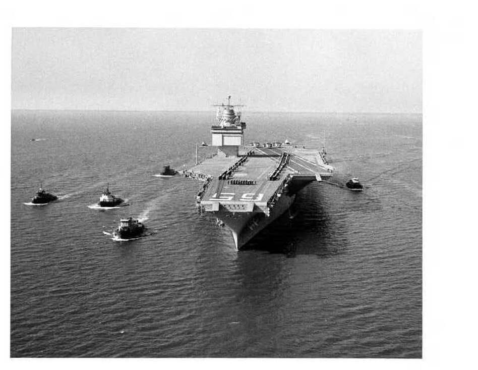 The world's largest ship, the nuclear-powered aircraft carrier USS Enterprise, is shown leaving Newport News, Va., with a five-tugboat escort during initial sea trials in 1961. (U.S. Navy)