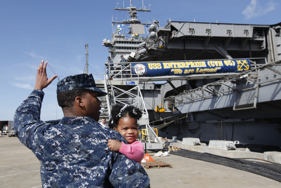 Petty Officer 3rd Class Michael Joseph carries his 1-year-old daughter, Maleah, to his re-enlistment ceremony aboard the USS Enterprise at the Norfolk Naval Station on March 8. The ship began its final deployment on March 11. (AP)