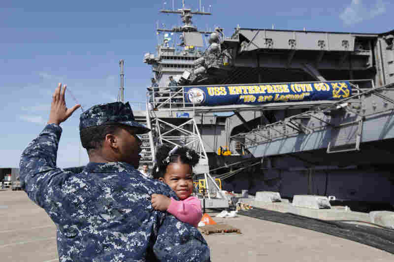 Petty Officer 3rd Class Michael Joseph carries his 1-year-old daughter, Maleah, to his re-enlistment ceremony aboard the USS Enterprise at the Norfolk Naval Station on March 8. The ship began its final deployment on March 11.