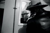 Bob Dylan checking a Halloween mask in the mirror, Plymouth, Mass., Rolling Thunder Revue tour, 1975.