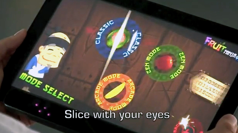 In an image from an Eye Tribe video, a man uses his eyes to play the Fruit Ninja game, slicing fruit in half as it appears on the screen. (The Eye Tribe)