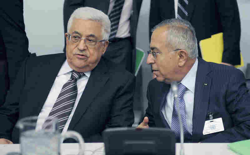 Palestinian President Mahmoud Abbas (left) talks to Palestinian Prime Minister Salam Fayyad prior to the U.N. General Assembly vote on Thursday.