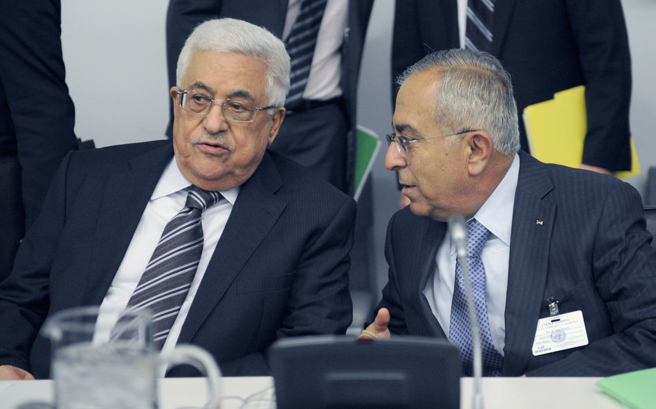 Palestinian President Mahmoud Abbas (left) talks to Palestinian Prime Minister Salam Fayyad prior to the U.N. General Assembly vote on Thursday. (AFP/Getty Images)
