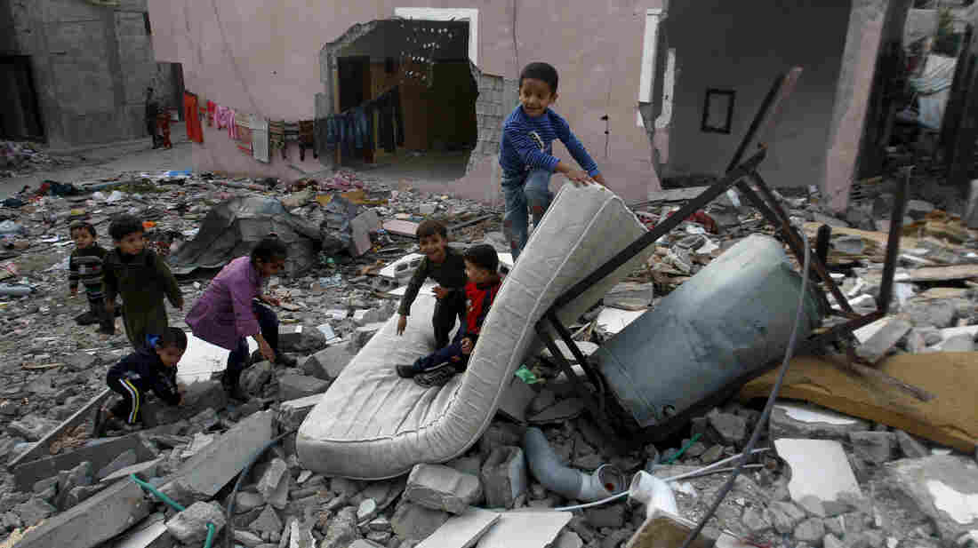 Palestinian children play in the rubble of a house that was hit by an Israeli strike during Israel's recent military offensive in the Gaza Strip Saturday.