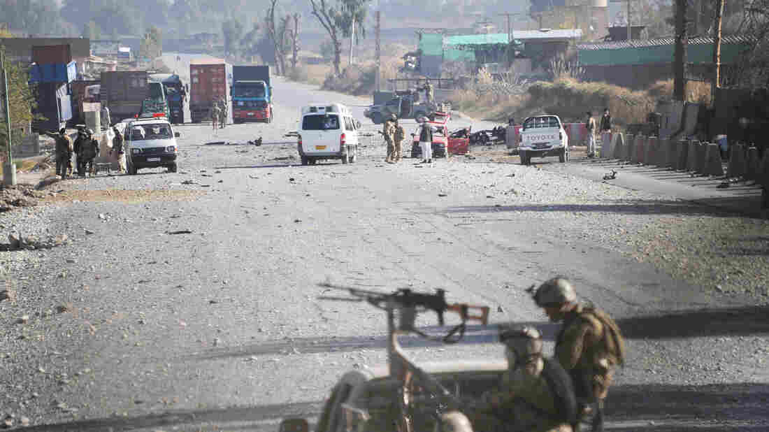 Afghan security forces block the road where Taliban suicide bombers attacked a joint U.S.- Afghan air base in Jalalabad, east of Kabul, Afghanistan on Sunday.