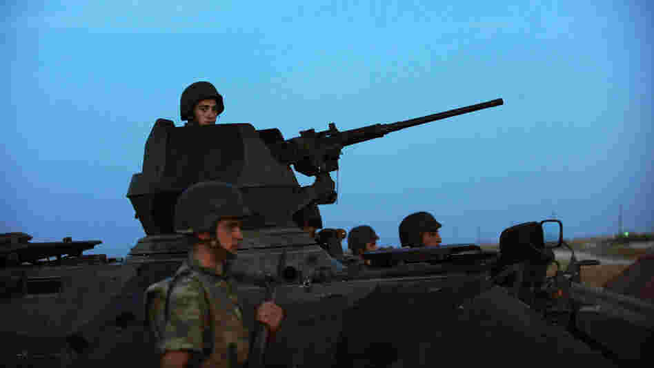 Turkish soldiers stand guard in the town of Akcakale, just across the border from Syria, on Oct. 4. The Turks have often issued stern warnings and retaliated when shooting from the Syrian war has come across their border. But Turkey did not respond to an incident over the weekend.