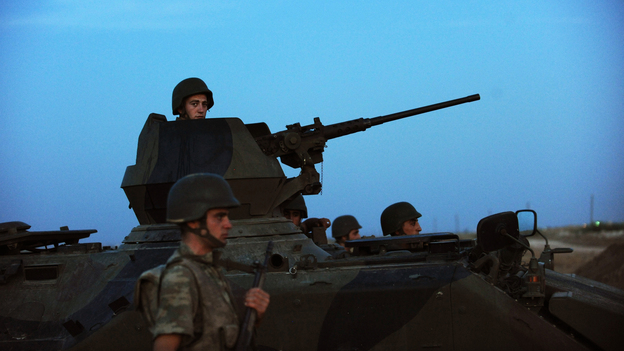 Turkish soldiers stand guard in the town of Akcakale, just across the border from Syria, on Oct. 4. The Turks have often issued stern warnings and retaliated when shooting from the Syrian war has come across their border. But Turkey did not respond to an incident over the weekend. (AFP/Getty Images)