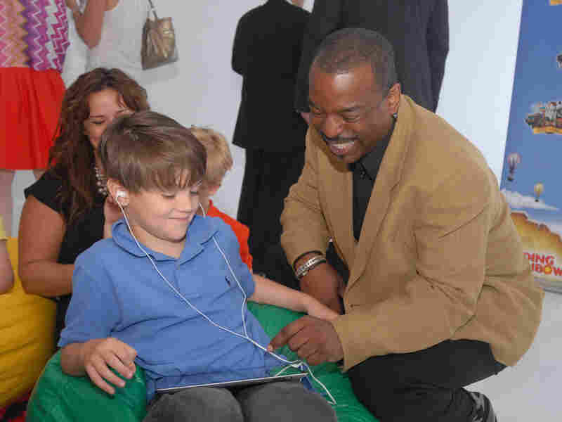 """LeVar Burton and 7 year old Shane Ammon exploring the all Reading Rainbow adventure app at the """"Reading Rainbow Relaunch"""" event in June."""