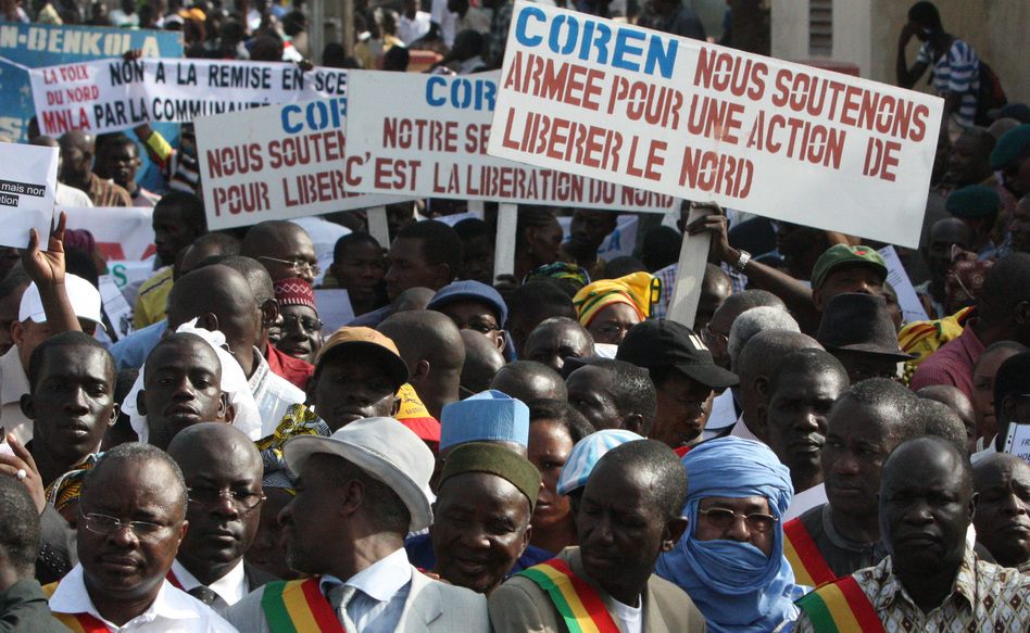 People originally from northern Mali carry signs that call for military action to retake that part of the country, now under the control of Islamist militants. The rally was held in Mali's capital, Bamako, in October.