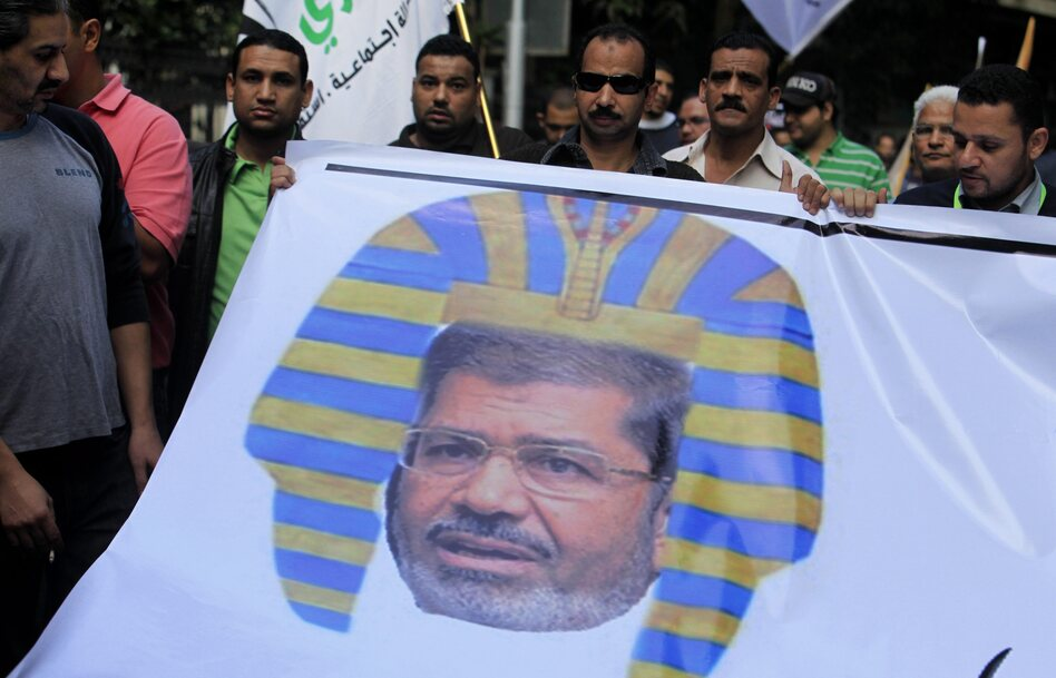 Egyptian protesters hold a banner depicting Morsi as a pharaoh, during a rally expressing opposition to Morsi's decrees, in Cairo, on Nov. 23.