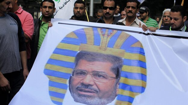 Egyptian protesters hold a banner depicting Morsi as a pharaoh, during a rally expressing opposition to Morsi's decrees, in Cairo, on Nov. 23. (EPA/Landov)
