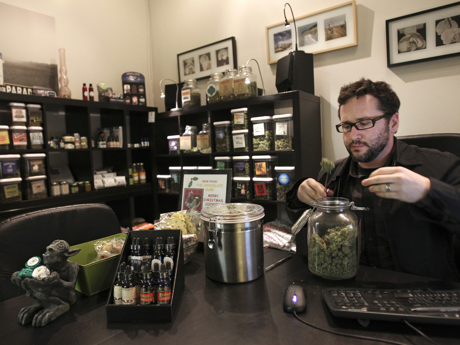 Chris Guthrie, vice president for operations at Canna Pi medical dispensary, inspects a medical marijuana product at his clinic in Seattle on Monday. Marijuana will be legal in Washington state from 12:01 a.m. Thursday.