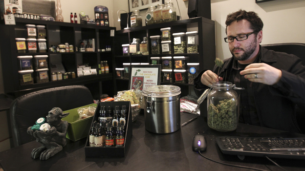 Chris Guthrie, vice president for operations at Canna Pi medical dispensary, inspects a medical marijuana product at his clinic in Seattle on Monday. Marijuana will be legal in Washington state from 12:01 a.m. Thursday. (Reuters /Landov)