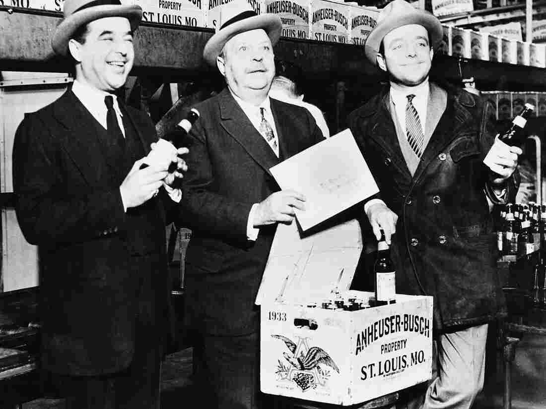 August A. Busch (center) and his sons, Adolphus III (left) and August Jr., seal the first case of beer off the Anheuser-Busch bottling p