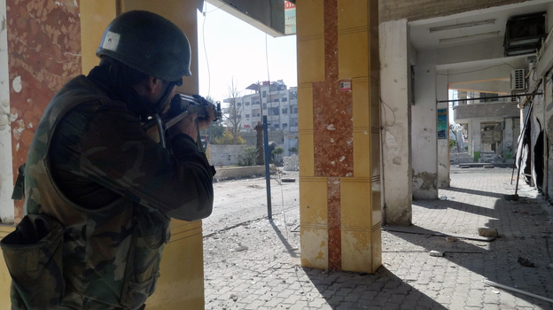 A Syrian soldier aims his rifle during clashes in the Damascus suburb of Daraya on Sunday. There is frequent fighting in and around Damascus, and residents are increasingly worried about a major battle for the capital. (AP/SANA)