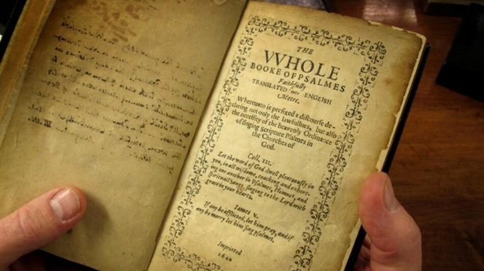 Jeff Makholm holds the Bay Psalm Book. (WBUR)