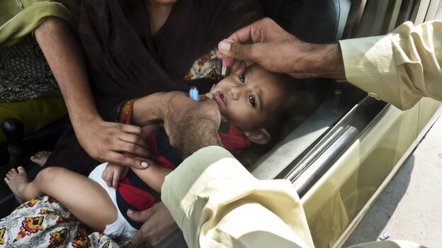 A child is inoculated with the polio vaccine at a traffic checkpoint j