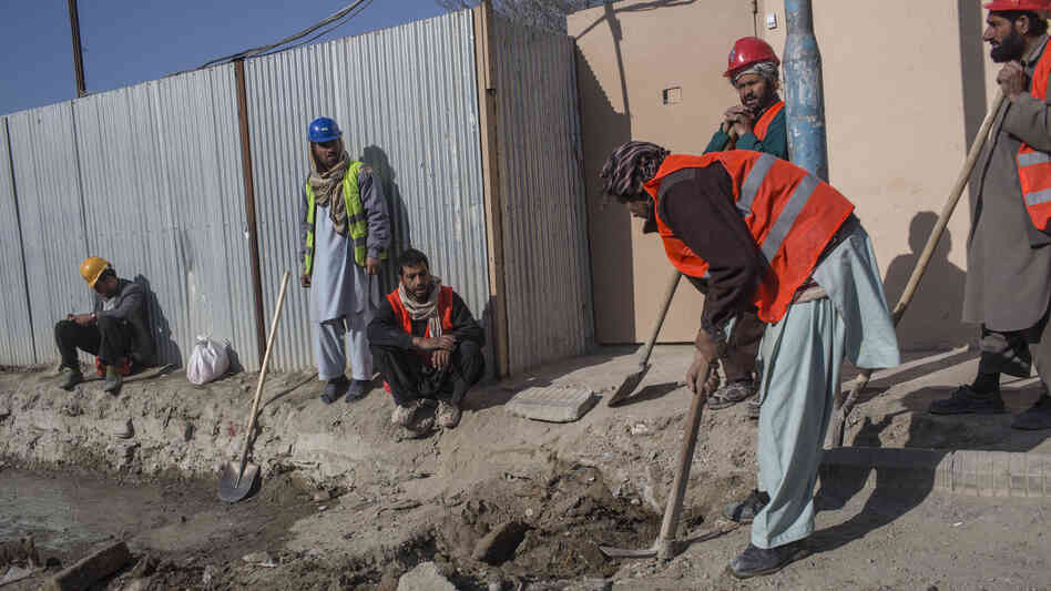 Afghan laborers work on a roads project last month in K