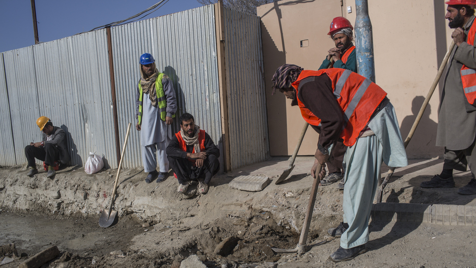 Afghan laborers work on a roads project last month in Kabul. A huge project to fix the city's roads and sewers is causing huge headaches.
