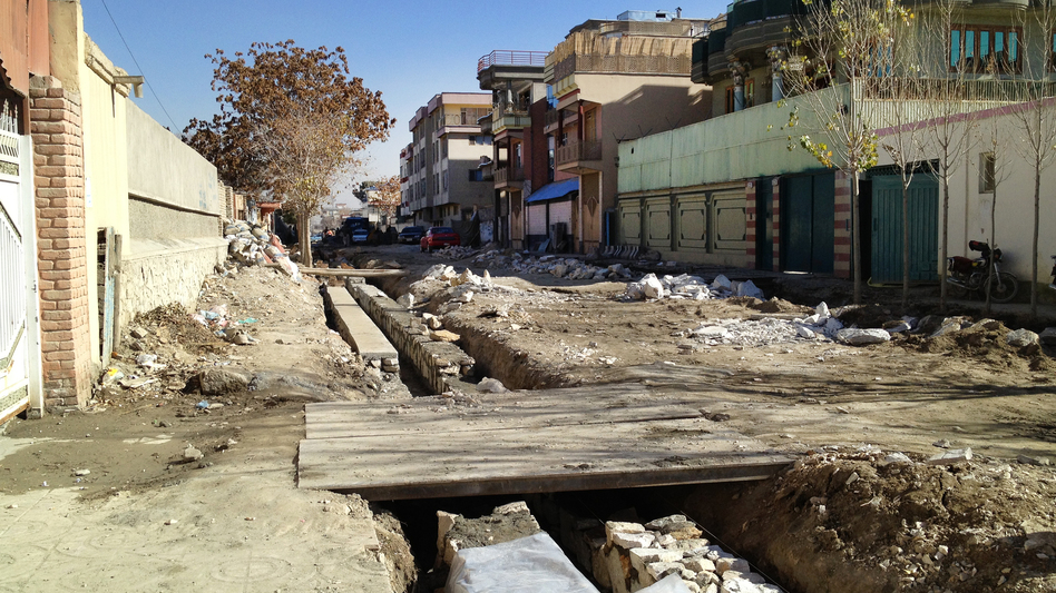 One of the streets undergoing renovation in Kabul. Residents often have to build makeshift bridges at their own expense to span the sewage trenches and reach their garages or driveways. (NPR)