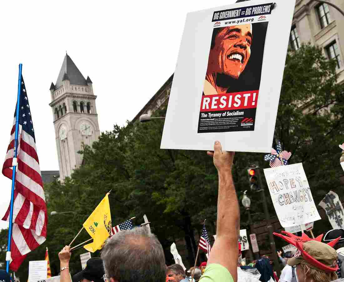 """A demonstrator carries a sign calling people to """"resist"""" President Barack Obama perceived socialist policies during a march of supporters of the conservative Tea Party movement in Washington."""