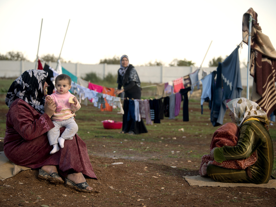 Mothers and their children sit among their washing in a refugee camp on the border between Syria and Turkey near the northern city of Azaz on Wednesday. The internally displaced faced further misery as heavy rain was followed by a drop in temperatures.